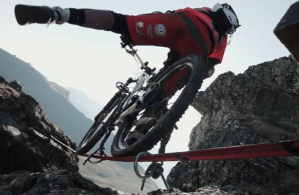 Mountain Biker Rides Between Two Cliffs on a Ribbon